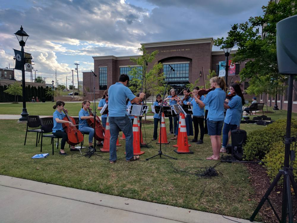 A conductor leads a group of young string players playing outside.