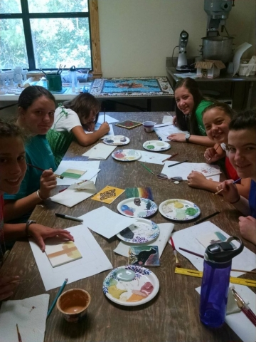 Children pause in their painting to look at the camera.