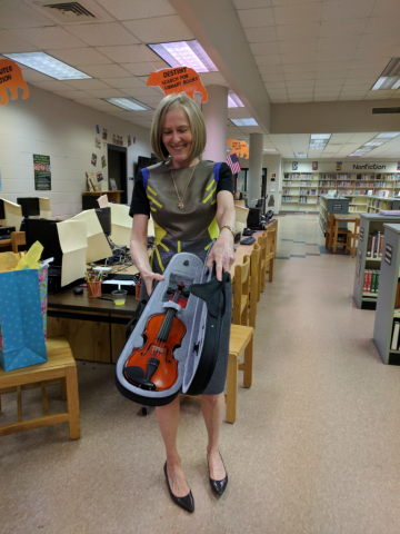A woman holds an open violin case, showing off the child's violin inside.