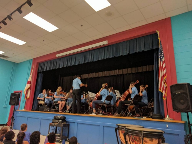 A symphony performs on stage at in an elementary school.
