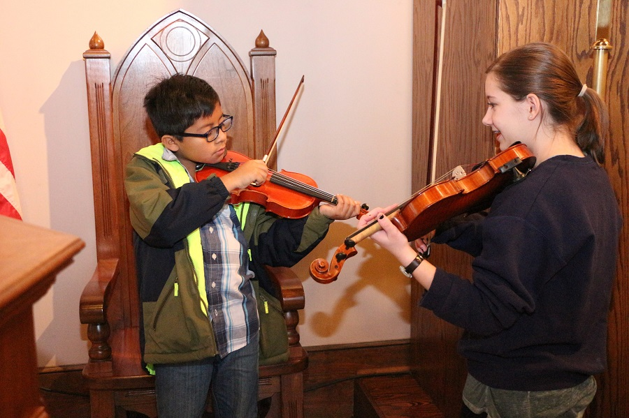 A young girl smiles holding her violin as she watches a younger boy play his violin