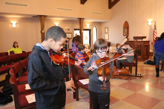 An older boy and younger boy play their violins together