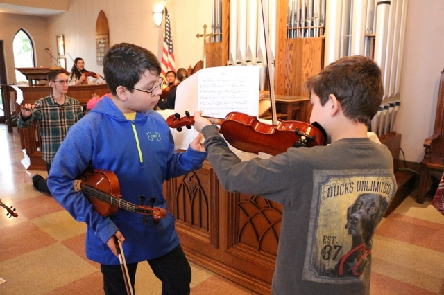 A boy holds the music for another boy as the other boy plays a violin